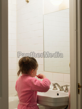 girl brushing her teeth in bathroom