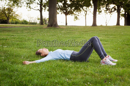 woman laying in grass at park