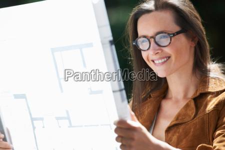 woman reading blueprints outdoors