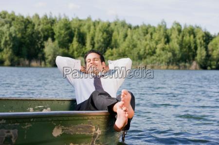 businessman lying in rowboat