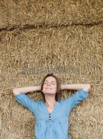 woman relaxing against hay bale