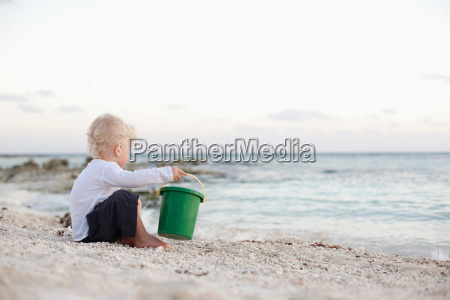 toddler boy playing with sand on