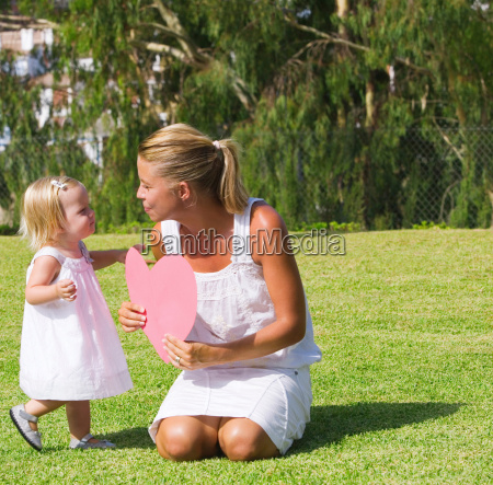 mother and daughter holding paper heart