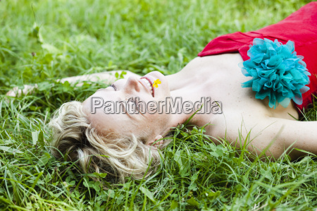 woman lying in grass eyes closed