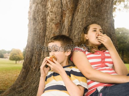 boy and girl eating apples against