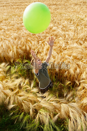 boy playing with balloon in wheat