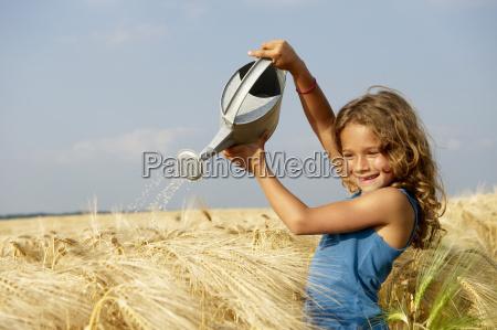 girl watering a wheat field