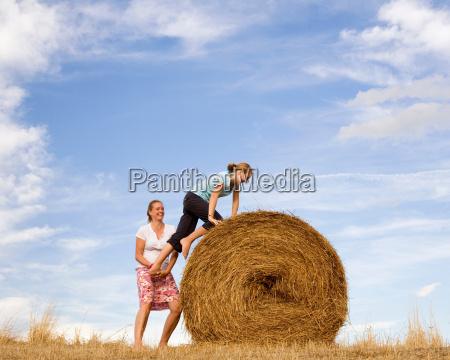 woman helping girl to climb hay