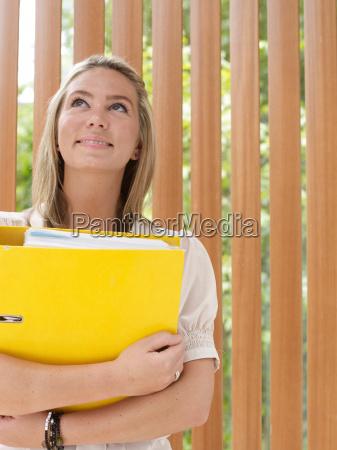 smiling businesswoman carrying folder