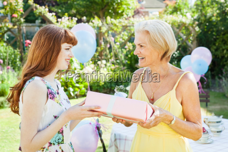 woman offers present to mature woman