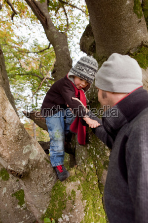 father helping son while climbing a