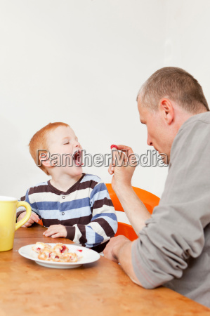 father and son playing at table