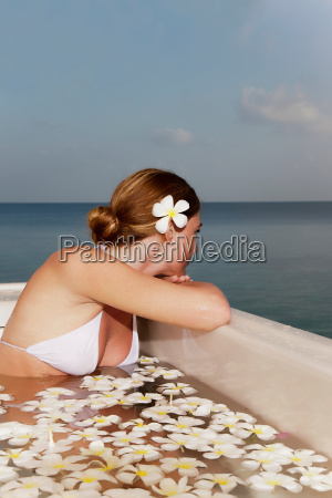 woman sitting in pool with flowers