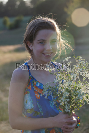girl holding bunch of flowers