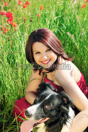 woman and dog sitting in field