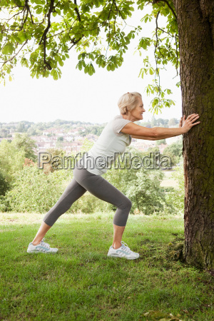 woman stretches leg holding onto tree