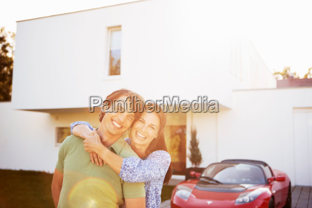 couple posing in front of house