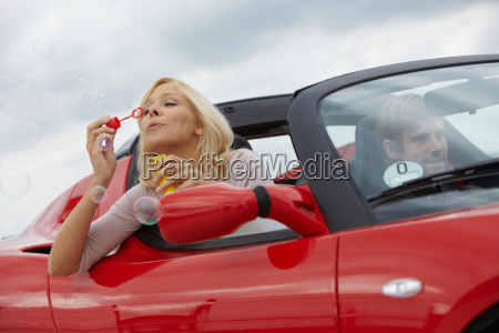 couple in electric car blowing bubbles