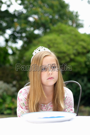 young girl with tiara on daydreaming