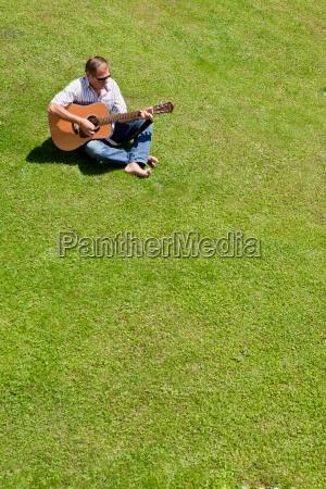 man playing guitar in grass