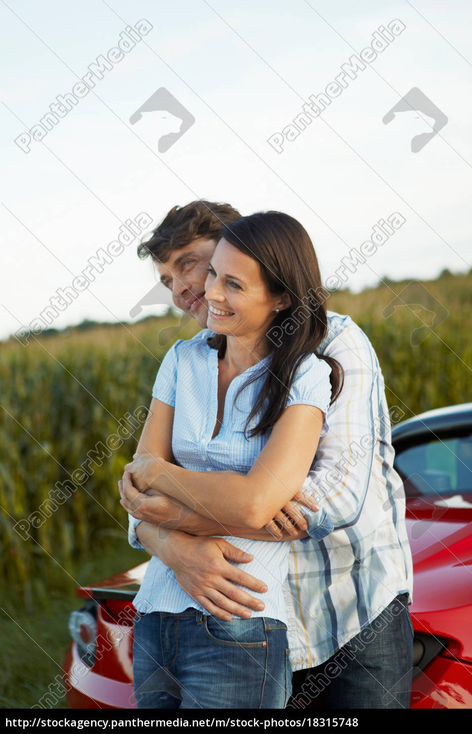 couple, standing, by, their, electric, car - 18315748