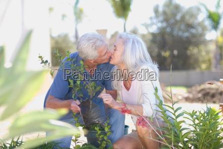 older couple kissing in garden