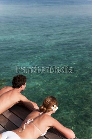 couple laying on deck overlooking sea