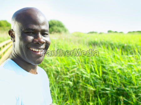 man smiling in field of flowers