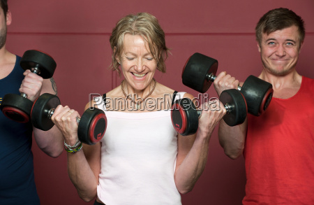 older people lifting weights in gym