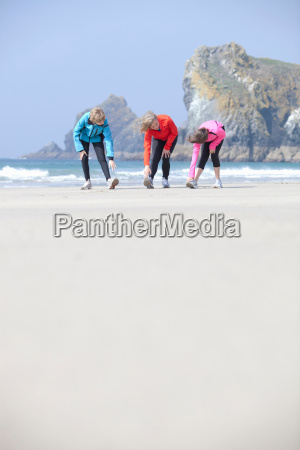 family stretching together on beach