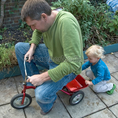 boy pushing father on tricycle
