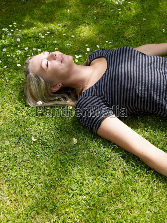 smiling woman laying in grass