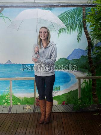 woman under umbrella with beach backdrop
