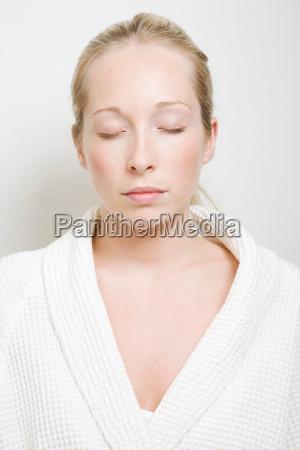woman wearing bathrobe with eyes closed