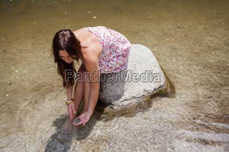 teenage girl sitting on rock in