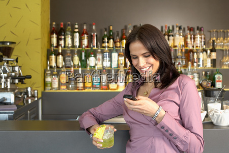 young woman texting leaning at bar