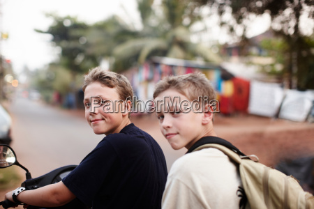 teenage boys riding scooter on dirt
