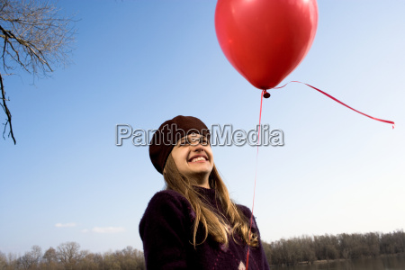 girl outdoors holding red balloon