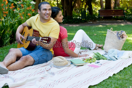 young couple sitting on picnic blanket