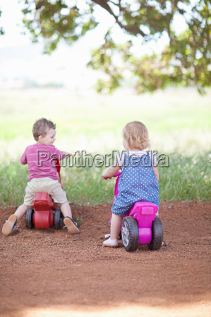toddlers riding toys on dirt road