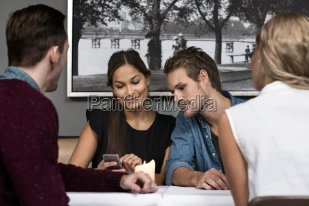 four young adult friends sitting in