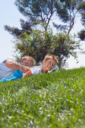 father and son playing on grass
