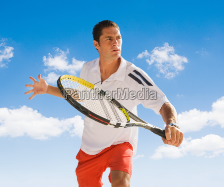 man playing tennis against blue sky