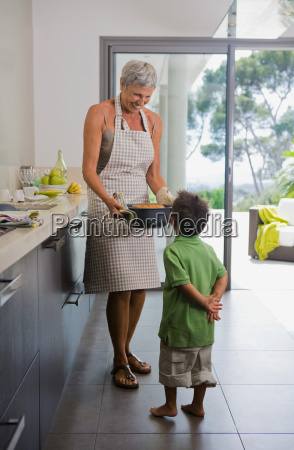 woman showing baking dish to boy