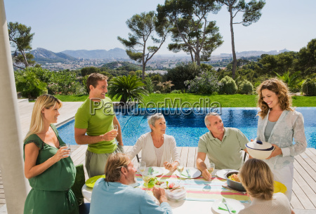 family eating by poolside
