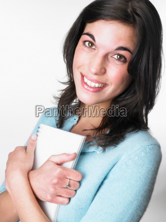 woman smiling holding a notebook