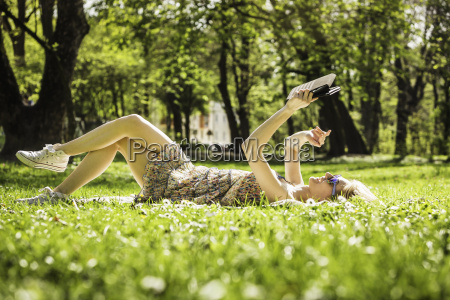 young woman lying in forest taking
