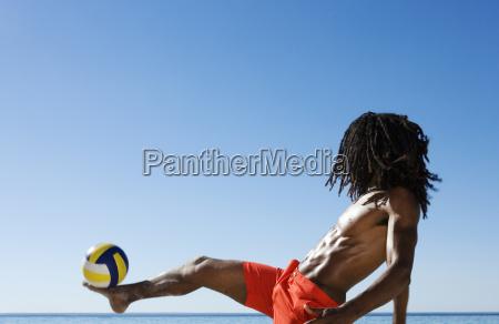 balancierender fussball des jungen mannes zu