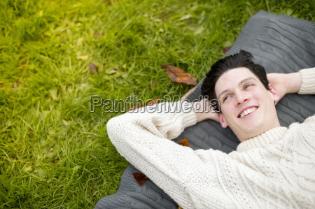 young man lying on rug wearing