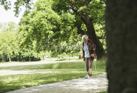 senior woman walking through park using